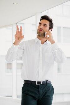 Um empresário está falando ao telefone e gesticulando