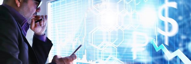 Um empresário está olhando para um gráfico em um monitor. um corretor de câmbio avalia as tendências do mercado de ações. um homem de óculos na frente de uma curva da dinâmica da economia.
