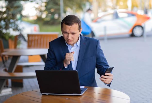 Um empresário está sentado à mesa de um café na rua, tosse na mão, fazendo uma videochamada em seu celular durante um intervalo no distrito financeiro. doença durante o trabalho.