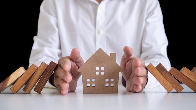 Um empresário ou mordomo usando a mão para proteger a casa da queda de um dominó de madeira. seguro de proteção da casa para estabilidade e segurança na vida e na propriedade.