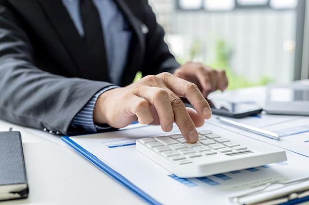 Um empresário pressiona uma calculadora para verificar os números dos documentos, é dono de uma empresa, verifica os documentos financeiros da empresa em seu escritório, as demonstrações financeiras. conceito de gestão financeira.
