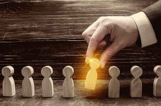 Um empresário puxa uma figura de homem dourado brilhante de uma multidão cinza. conceito de busca por contratação