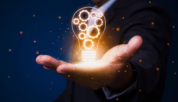 Um empresário que segura uma lâmpada com uma engrenagem interna demonstra a visão