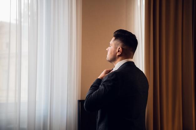 Um empresário se arrumando para uma reunião, consertando a gravata, parado em frente à janela em um luxuoso banheiro do quarto de hotel