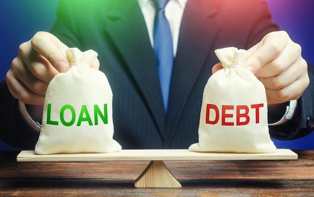 Um empresário segura bolsas com um empréstimo e dívidas em escalas