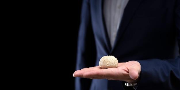 Um empresário segura na mão um modelo de um cérebro feito de argila de polímero em um fundo escuro
