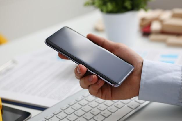 Um empresário segura um novo smartphone na mão o mercado de aplicativos para dispositivos móveis mostra uma tela na qual você pode inserir sua imagem para publicidade ou estatísticas financeiras.