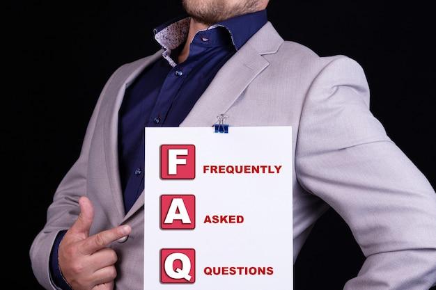 Um empresário segura uma folha de papel em branco com o texto abreviado como faq perguntas mais frequentes.