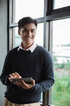 Um empresário segurando o tablet digital olha para a câmera na frente das janelas