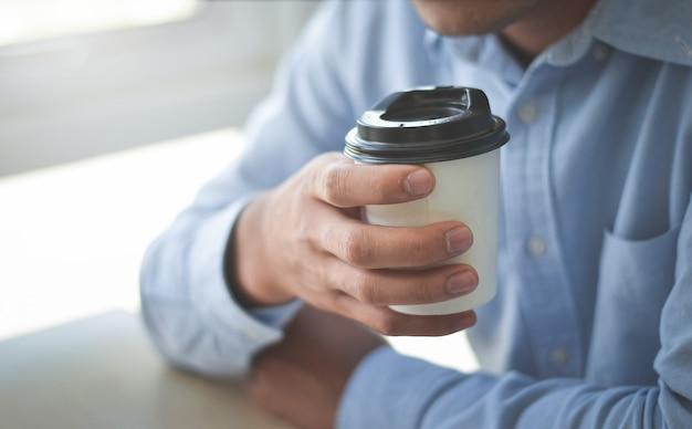 Um empresário sentado em uma cafeteria tomando café com as luzes no parapeito da janela.