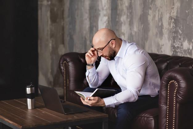 Um empresário verifica informações em um notebook enquanto trabalha com um laptop no escritório