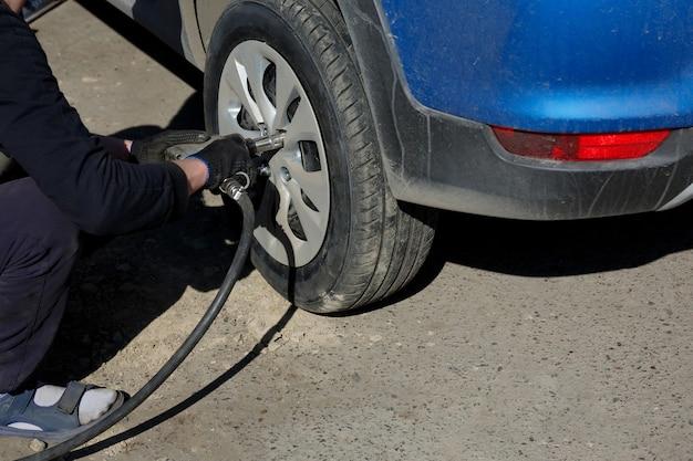 Um encaixe de pneu aparafusa as porcas da roda com uma chave pneumática