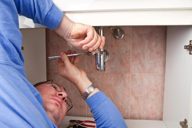 Um encanador consertando uma pia quebrada no banheiro