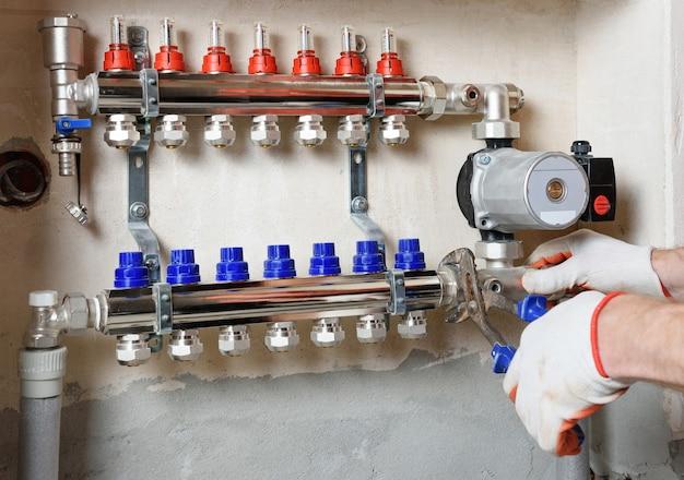 Um encanador está consertando uma bomba d'água em um sistema de aquecimento de piso.