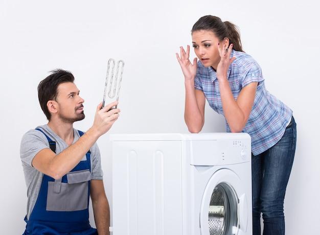 Um encanador masculino veio para consertar uma máquina de lavar roupa.
