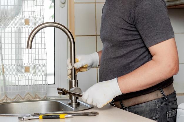 Um encanador na cozinha instala uma nova torneira de água. conserto da torneira da cozinha perto da pia Foto Premium