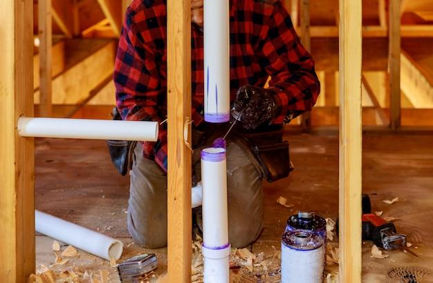 Um encanador que aplica o primer e cola um conjunto de drenagem de tubos de pvc