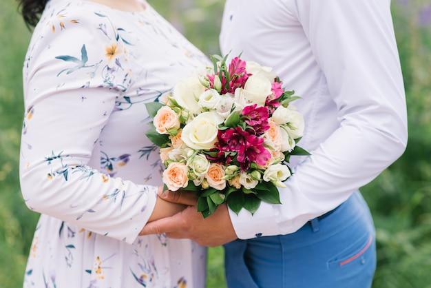 Um encontro romântico de um cara e uma menina, um close de um buquê de flores, um presente para uma menina. noiva e noivo. buquê de casamento