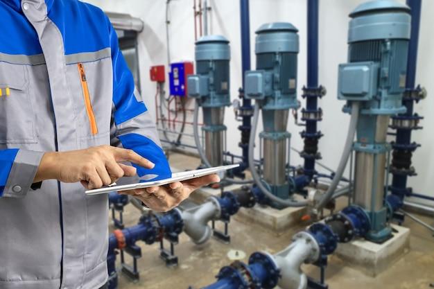 Um engenheiro com um tablet inspecione o dispositivo de backup do gerador de eletricidade industrial