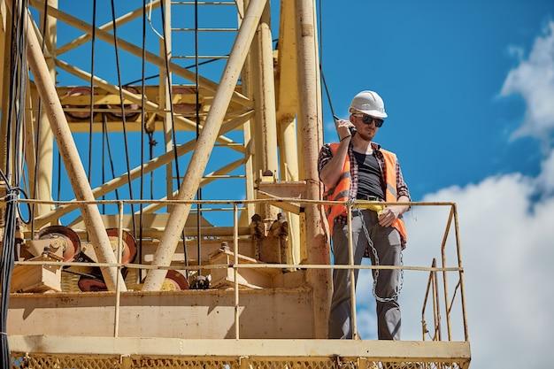 Um engenheiro de construção com uma camisa xadrez, colete laranja e capacete branco em um guindaste de construção amarelo com um walkie-talkie nas mãos. capataz, supervisor, trabalhador