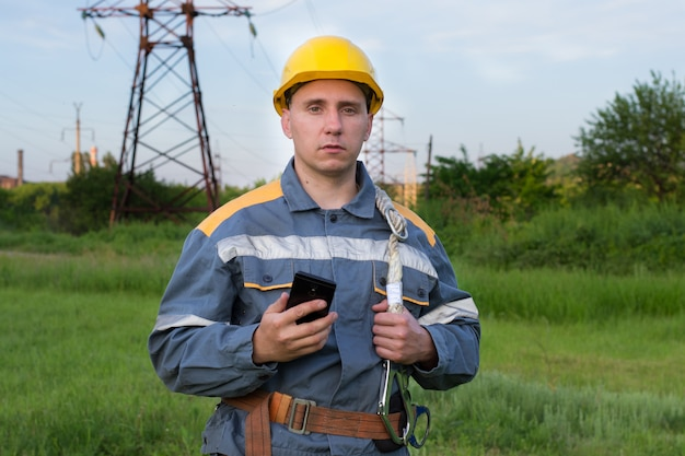 Um engenheiro de energia com um telefone celular nas mãos.