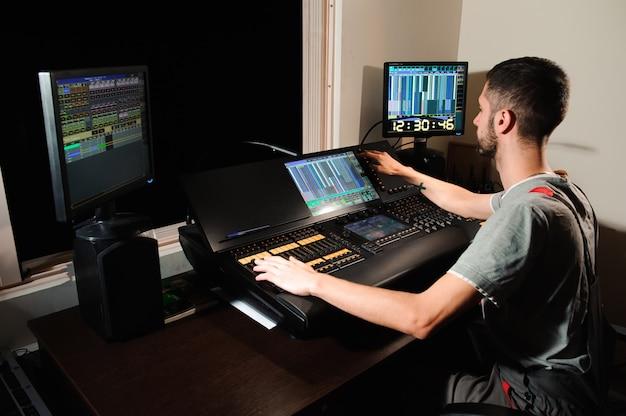 Um engenheiro de iluminação trabalha com controle de técnicos de luzes