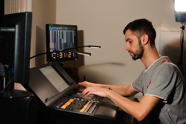Um engenheiro de iluminação trabalha com o controle de técnicos de luzes no show de concertos. misturador de luz profissional, console de mixagem. equipamento para shows.
