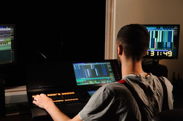 Um engenheiro de iluminação trabalha com o controle de técnicos de luzes