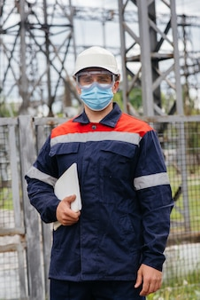 Um engenheiro de subestação elétrica inspeciona equipamentos modernos de alta tensão em uma máscara no momento da pandemia. energia. indústria.
