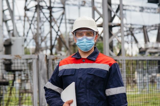 Um engenheiro de subestação elétrica inspeciona equipamentos modernos de alta tensão em uma máscara no momento da pondemia. energia. indústria.