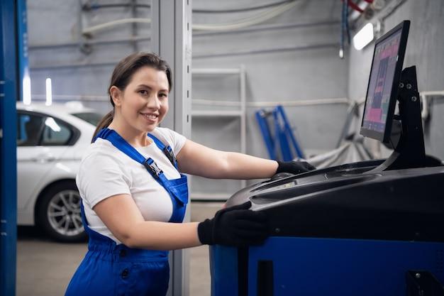 Um engenheiro usa um computador para trabalhar em uma oficina e sorrindo