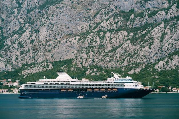 Um enorme cruzeiro de vários andares na baía de kotor, tendo como pano de fundo uma montanha acima da cidade de