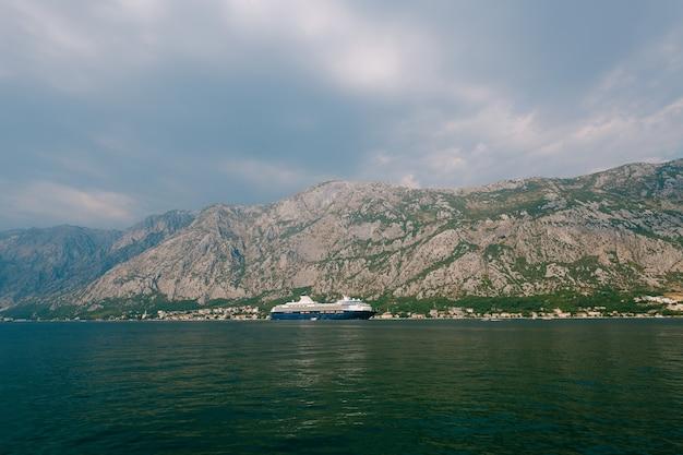 Um enorme cruzeiro de vários andares na baía de kotor tendo como pano de fundo uma montanha