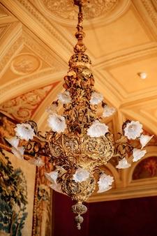 Um enorme lustre dourado antigo com cortinas brancas com lâmpadas no teto com molduras de estuque