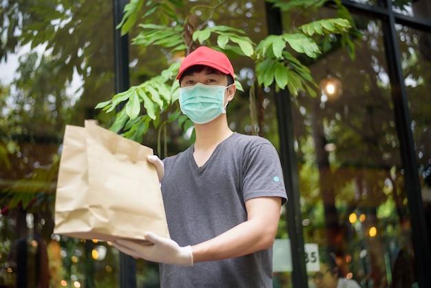 Um entregador asiático está usando máscara facial, segurando a sacola de compras, conceito de entrega em domicílio de segurança