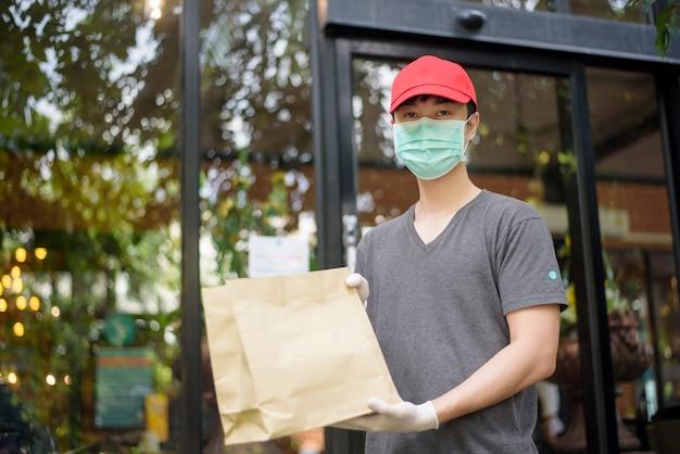 Um entregador asiático está usando máscara facial, segurando sacola de compras