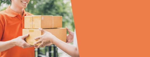 Um entregador de camisa polo laranja dando uma encomenda a um cliente