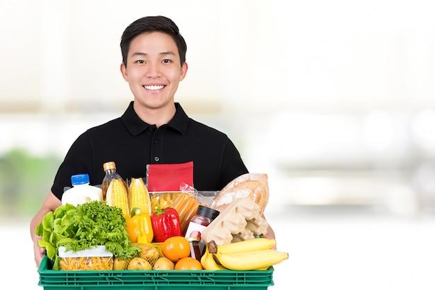 Um entregador de supermercado asiático vestindo um poloshirt preto segurando cesta de alimentos