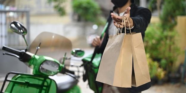 Um entregador está segurando uma sacola de papel ao lado de sua motocicleta.
