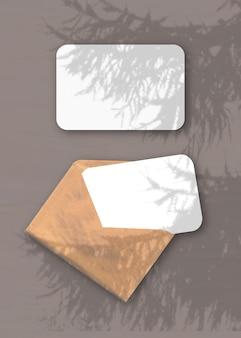 Um envelope com duas folhas de papel texturizado branco no fundo marrom sobreposição de maquete com as sombras das plantas
