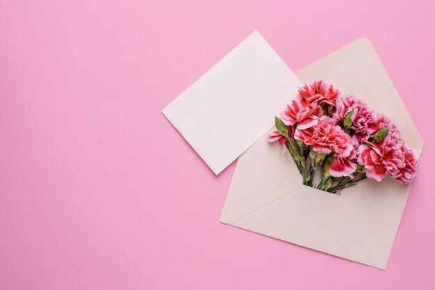 Um envelope com flores cor de rosa e um cartão de presente em rosa