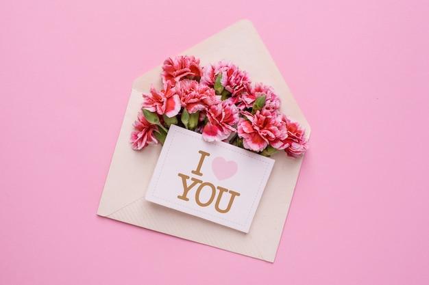 Um envelope com flores cor de rosa e um cartão eu te amo em rosa