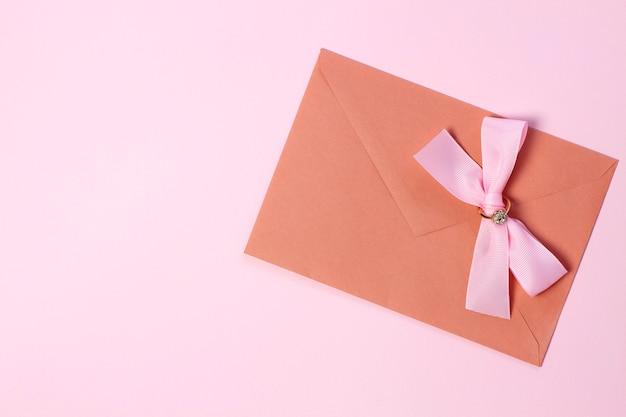Um envelope com um laço rosa em um fundo rosa pastel.