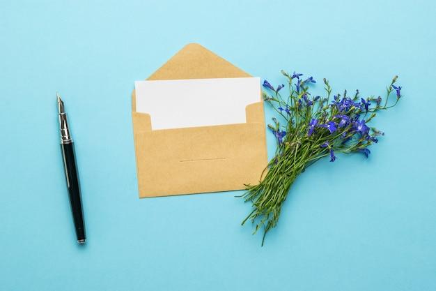 Um envelope com uma carta, uma caneta-tinteiro e um buquê de flores sobre fundo azul. postura plana.