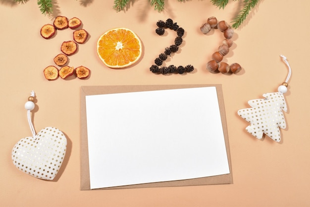 Um envelope e uma folha em branco sobre fundo bege com os números 2022 feitos de materiais naturais