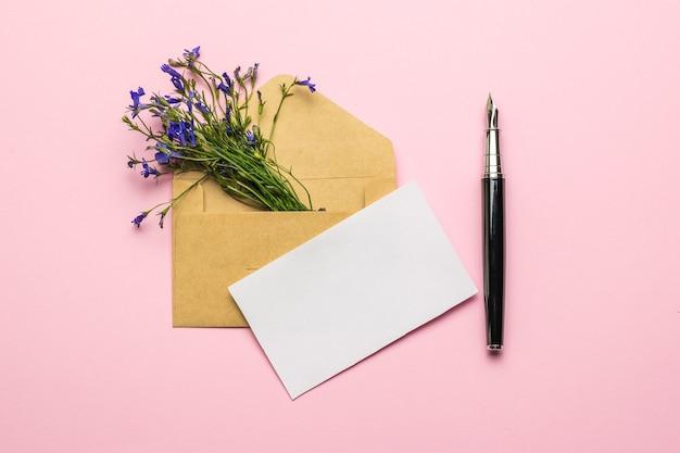 Um envelope, uma folha de papel, uma caneta-tinteiro e um buquê de flores em um fundo rosa. postura plana.