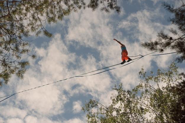 Um equilibrista caminha ao longo da linha alta contra o fundo de um céu