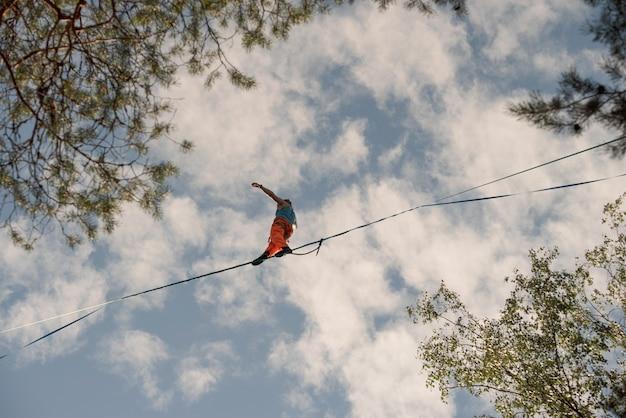 Um equilibrista caminha ao longo da linha alta sobre as árvores
