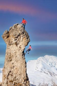Um escalador no topo faz seu parceiro descer a corda