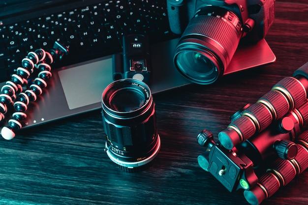 Um espaço de trabalho com laptop, câmera moderna, lente, tripé e uma caneta